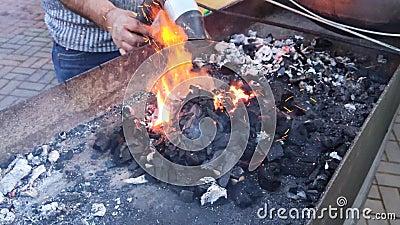 Um homem sopra um secador de cabelo em carvão quente num churrasco Carne cozinhada ao ar livre Conceito de Lifehack de Barbecue vídeos de arquivo