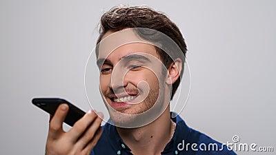 Um homem sorridente gravando mensagem de voz no smartphone Homem feliz usando telefone celular filme