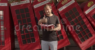 Um homem sorridente mostrando polegares para cima, de pé contra o telefone britânico, estudando inglês vídeos de arquivo