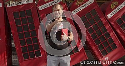 Um homem sorridente mostrando polegares para cima, de pé contra o telefone britânico, estudando inglês video estoque
