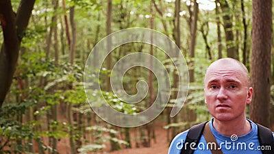 Um homem turista com mochila perdida numa floresta Ele tem medo e medo, olhando em volta filme