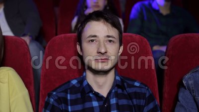 Um indivíduo emocional novo olha um filme triste em um cinema e em gritos, retrato video estoque
