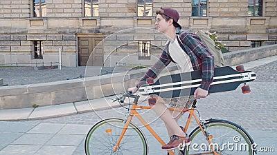 Um indivíduo feliz que monta uma bicicleta com um skate em sua mão na área urbana filme