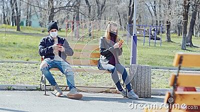 Um jovem casal sentado em um banco com máscaras médicas a distância tira uma selfie filme