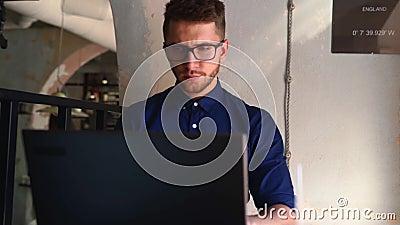 Um jovem e atraente hipster freelancer trabalhando remotamente em laptop em loft cafe Businessman navegando na internet no caixei filme