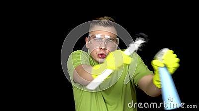 Um jovem limpador de sanita está dançando Homem com óculos de segurança e luvas para limpeza da casa de banho O cara segura um ba filme