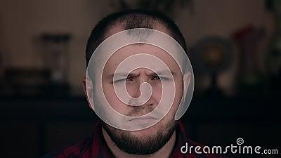 Um jovem ofendido, que aparenta ser europeu, senta-se numa cadeira com camisa calça Conceito de emoção vídeos de arquivo
