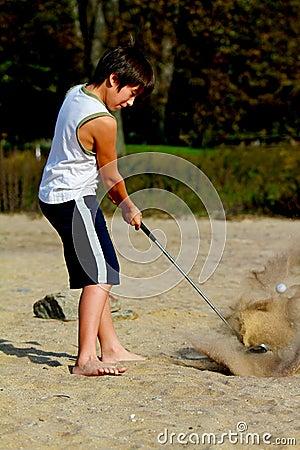 Um menino 10 bate uma esfera de golfe na praia