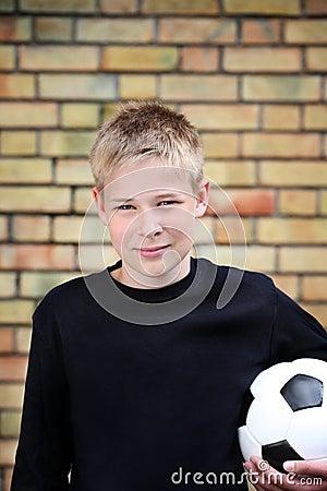 Um menino de encontro a uma parede com uma esfera