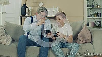 Um menino e seu avô observam joysticks de console video estoque