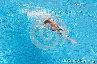 Um menino está nadando o curso de borboleta
