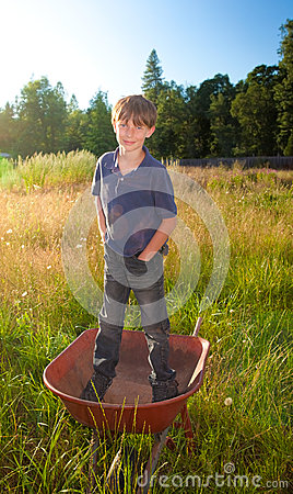 Um menino novo da vida real que está em um carrinho de mão