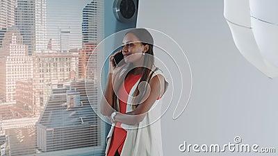 Um modelo africano atrativo falando com alguém no smartphone durante o intervalo de fotos no estúdio filme