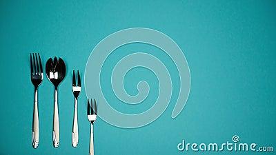 Um número forquilhas e de colheres para pratos diferentes filme