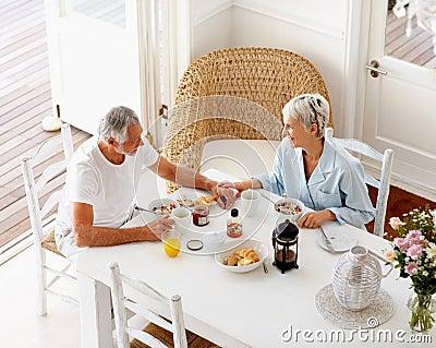 Um par envelhecido que aprecia seu pequeno almoço em casa