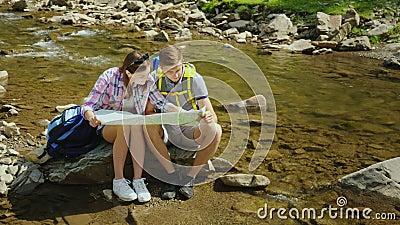 Um par novo está sentando-se em uma rocha perto de um rio da montanha Olham o mapa junto Planeando a rota e filme