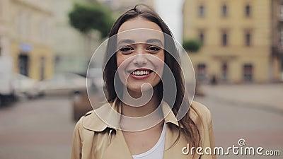Um retrato de uma jovem atraente vestindo trincheira parecendo feliz sorrindo e rindo do fundo da cidade perto vídeos de arquivo