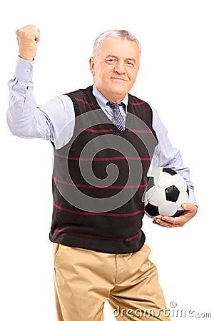 Um ventilador maduro feliz com futebol que gesticula com sua mão