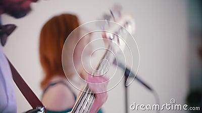 Uma banda musical que grava uma canção no estúdio - mulher gengibre adulta cantando e homem brest tocando sua parte video estoque