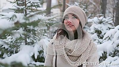 Uma bela jovem de bom humor caminha pela floresta de inverno, olha para as árvores de Natal na neve e vídeos de arquivo