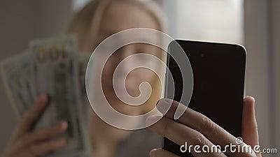 Uma blogueira fala sobre negócios e finanças ao fazer vídeos online em um smartphone Na mão da mulher está uma mão filme