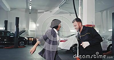 Uma boa empresária de terno e o mecânico atraente parecem dançar numa garagem depois de terminarem. video estoque