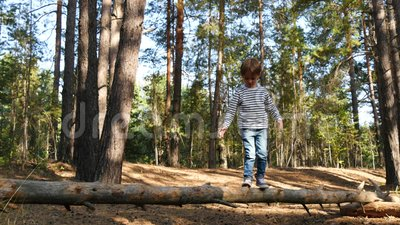 Uma criança feliz passa tempo jogando ao ar livre no parque ou o garoto ativo está caminhando no feixe para superar obstáculos vídeos de arquivo