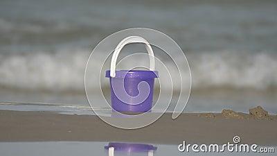 Uma cubeta roxa do brinquedo na areia na praia com as ondas efervescentes no fundo video estoque