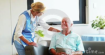 Uma enfermeira que visita um paciente superior video estoque