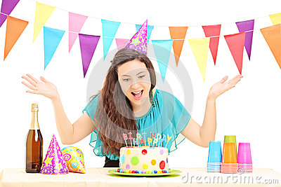 Uma fêmea do feliz aniversario com um chapéu do partido que gesticula com sua mão