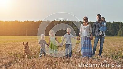 Uma grande família de seis pessoas se coloca no campo com um pastor video estoque