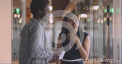 Uma jovem empresária asiática amistosa a falar com o colégio africano americano vídeos de arquivo