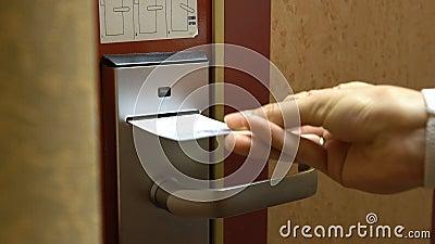 Uma jovem mulher abre a porta de sua sala de hotel usando um cartão chave eletrônico vídeos de arquivo