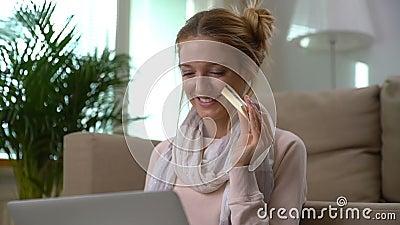 Uma jovem mulher bonita usa o assento em linha dourado do cartão de crédito no assoalho Tiro da zorra video estoque