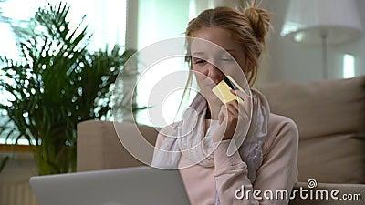 Uma jovem mulher bonita usa o assento em linha dourado do cartão de crédito no assoalho Tiro da zorra vídeos de arquivo