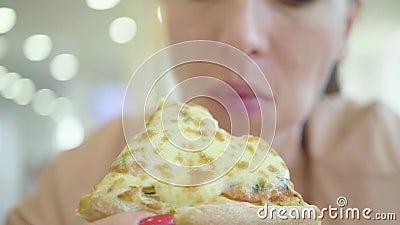 Uma jovem mulher est? comendo uma parte de pizza Riso feliz de encantamento da menina e mordedura fora da fatia grande de pizza f video estoque