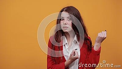 Uma jovem séria de camisa branca e jaqueta vermelha que mantém punhos levantados, brigando, dançando video estoque