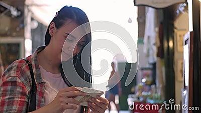 Uma jovem sorrindo ao olhar para o artesanato de papel num mercado video estoque