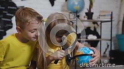 Uma menina bonita com um menino através da lupa olha o globo na sala de aula Em uma lição da geografia vídeos de arquivo
