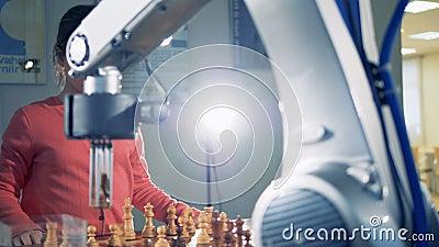 Uma menina de cabelo escura pequena está jogando a xadrez com um braço robótico video estoque