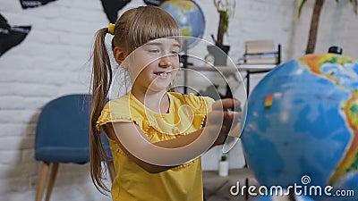 Uma menina doce em um t-shirt amarelo senta-se na tabela na sala de aula da geografia e está estudando curiosamente o globo ou video estoque