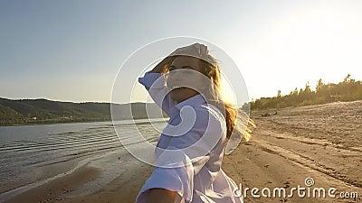 Uma menina e um indivíduo que correm ao redor na praia filme