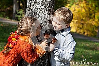 Uma menina e um menino estão jogando o hide-and-seek