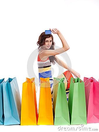 Uma menina em uma cor longa do vestido com sacos de compra