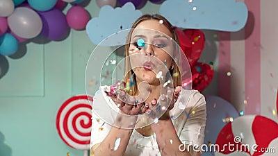 Uma menina feliz funde em um ouropel ou em um confete em uma sala com doces enormes vídeos de arquivo