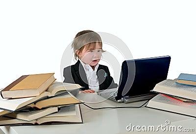 Uma menina pequena (menino) que trabalha no computador.