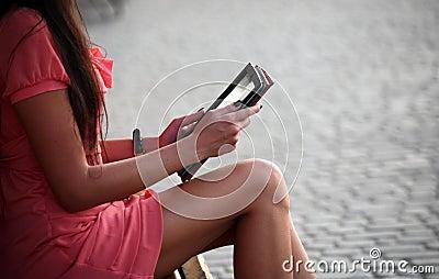 Uma menina que senta-se em um banco e que lê um livro