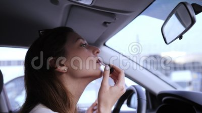 Uma moça bonita aplica batom ao carro Maquiagem antes do trabalho Balão de lábios video estoque