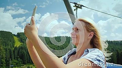 Uma mulher ativa na cabine de um elevador de esqui, de umas opiniões bonitas das fotografias das montanhas e de umas florestas Fe vídeos de arquivo
