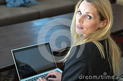 Uma mulher de negócio nova que usa uma parte superior do regaço